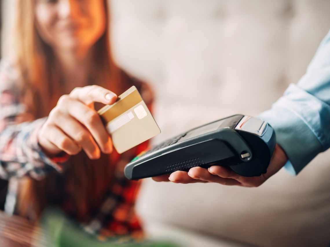 small business owner swiping her card in a credit card processor