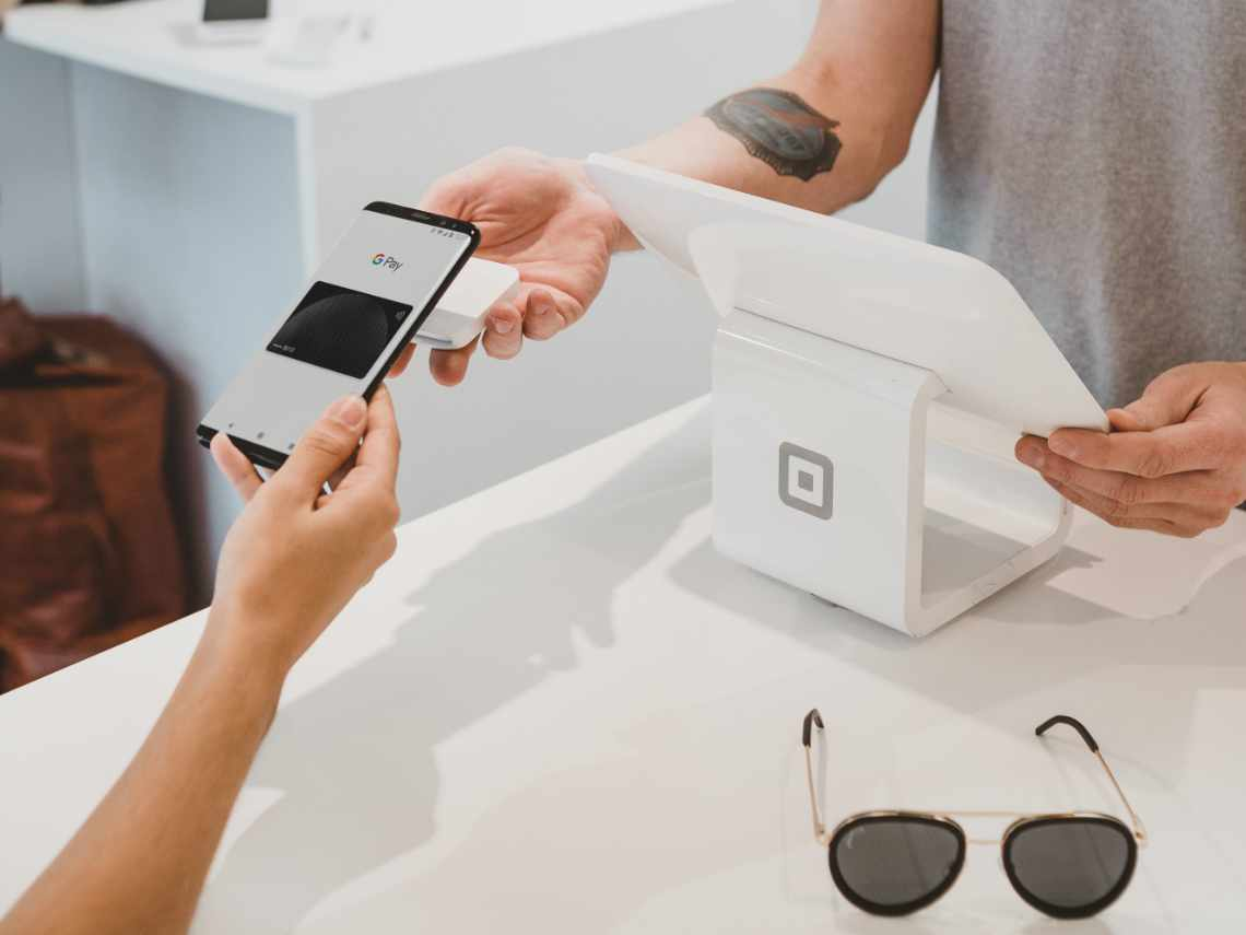 man making a contactless payment at a retail store