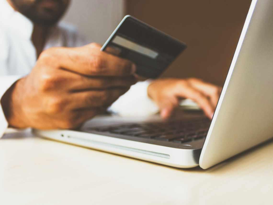 man sitting at computer purchasing something online